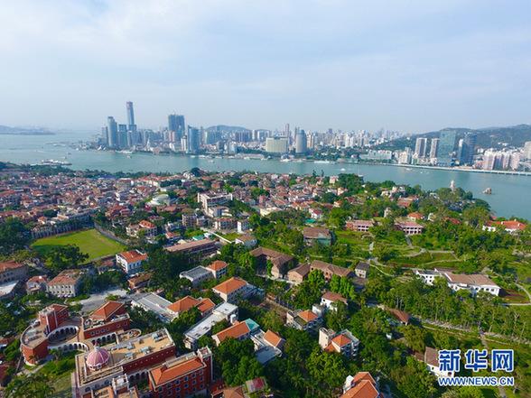 空中俯瞰鼓浪屿上的传统建筑群与远处厦门岛上的现代建筑群遥相辉映