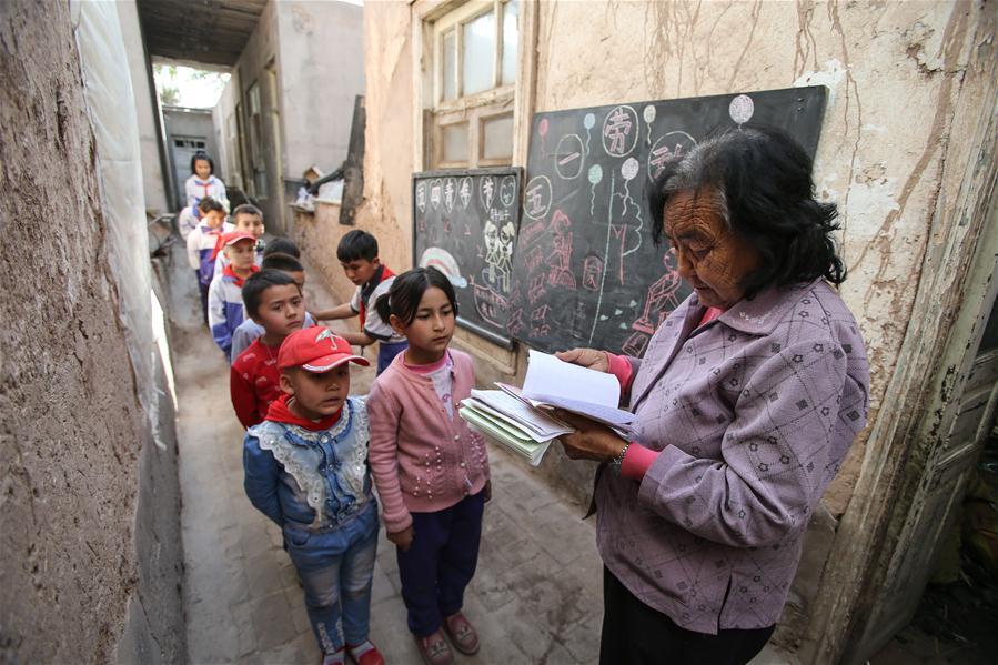 """潘玉莲在疏勒县""""爱心小课堂""""上课前检查孩子们的作业(4月24日摄)."""