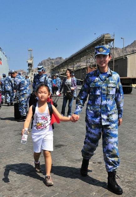 2015年3月,也門,海軍女戰士牽著一名小女孩的手準備登上軍艦。