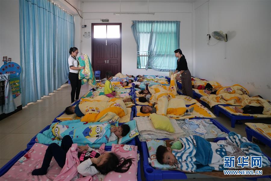 在中山市三乡镇雍陌幼儿园,廖鸿慧(左)照顾孩子们午休(11月20日摄).